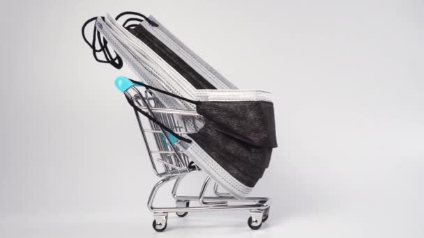 Shopping cart in a medical disposable mask loaded with black medical protective masks on a white background. Medical supplies concept. Miniature. Close-up