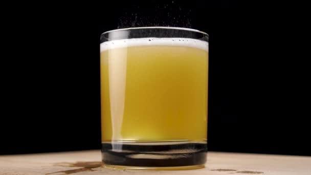 Sklenici moštu s pěnou a bublinkami po nalití nízkého lihového jablečného nápoje. Na černém pozadí. Na prknech. Zpomalený pohyb