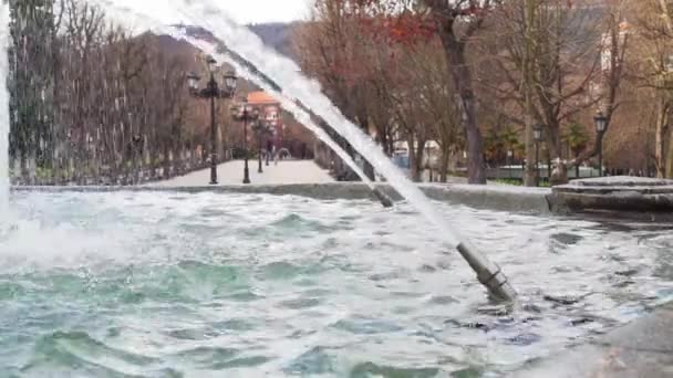 Fountain with nozzles and jets of water on the alley of the autumn old park with antique lanterns against the background of mountains