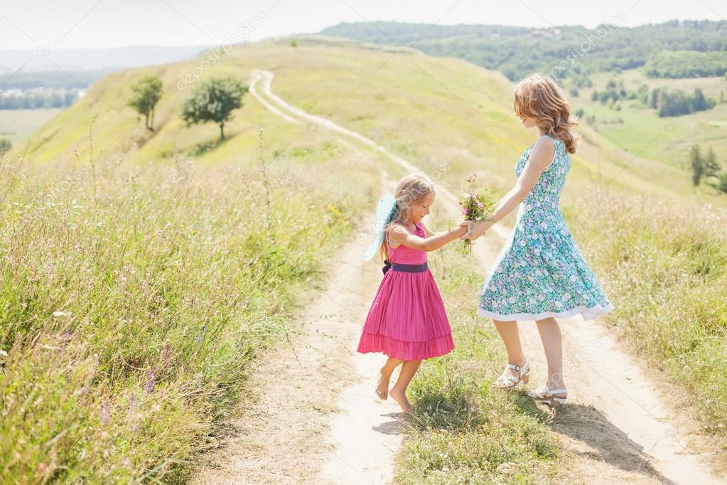 Mother and daughter dancing  on the meadow