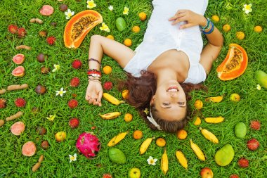 Woman lying  with fresh exotic fruits