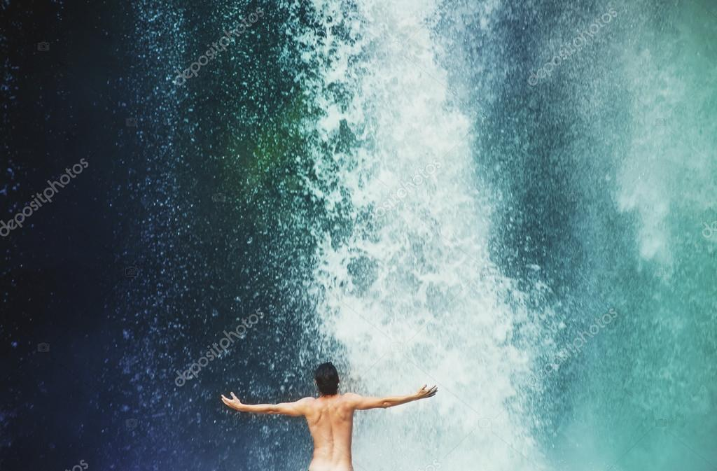 Man refreshing in waterfall