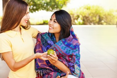 woman giving food to poor  woman