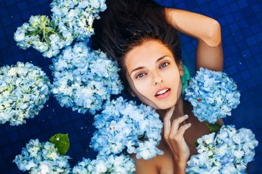 woman in swimming pool full of hortensia