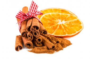 Dried orange slices with cinnamon sticks and cinnamon powder on white.