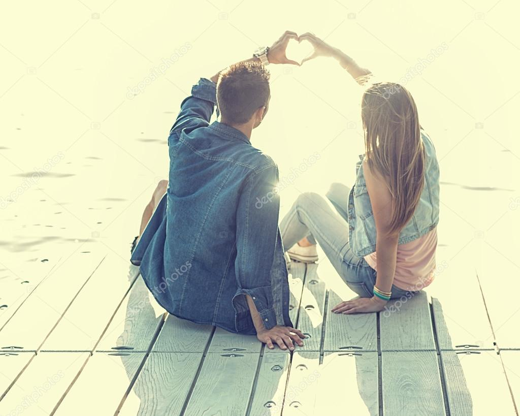 Couple in love sitting on pier