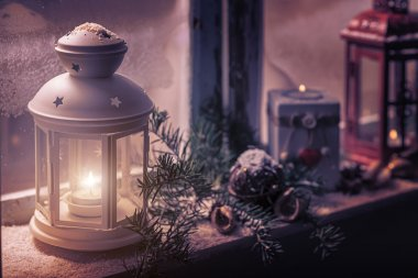 candles glow in steamy window