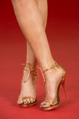 Sexy legs in gold high heels on the red carpet