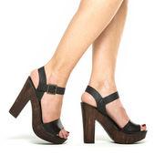 Fotografia Piedini femminili in scarpe tacchi alti con suola in legno piattaforma