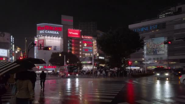 tokyo, japan - october 25 2019: Pan right video of people and cars waiting at fire of the crossing of JR Shinjuku East Exit Station Square wet by rain and reflecting illuminated skyscrapers at night.