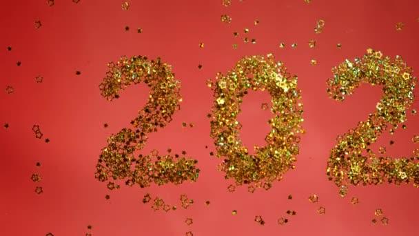 Arany 2021-es számok. 4k videó. Ünnepeljük az új évet. Vörös szín. Csillámcsillag alakú