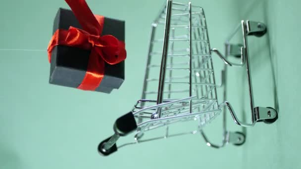 Levitate gift box with red ribbon bow. Shopping cart. Turquoise background. Holiday sale. Seasonal discount. Vertical 4k video