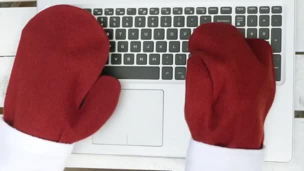Horní pohled Santa v červených rukavicích psaní na klávesnici notebooku. 4k video. Vánoční prodej.