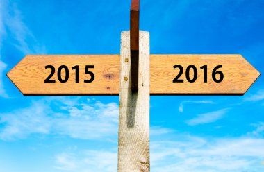 Wooden signpost with two opposite arrows over clear blue sky, year 2015 and 2016 signs, Happy New Year conceptual image