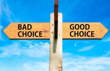 Wooden signpost with two opposite arrows over clear blue sky, Bad Choice and Good Choice messages, Right choice conceptual image