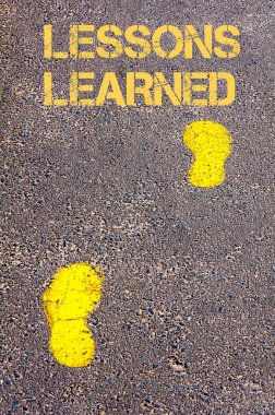 Yellow footsteps on sidewalk towards Lessons Learned message