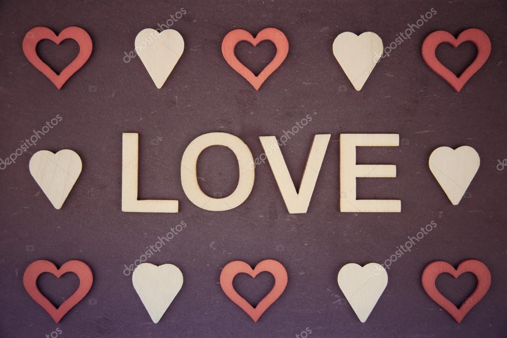 Word Love Created Of Wood Letters Over Vintage Chalkboard With Red