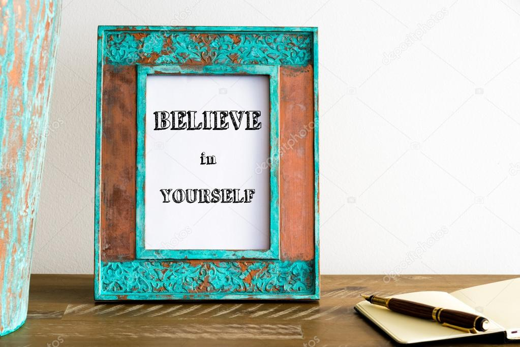 Vintage photo frame on wooden table with text BELIEVE IN YOURSELF ...