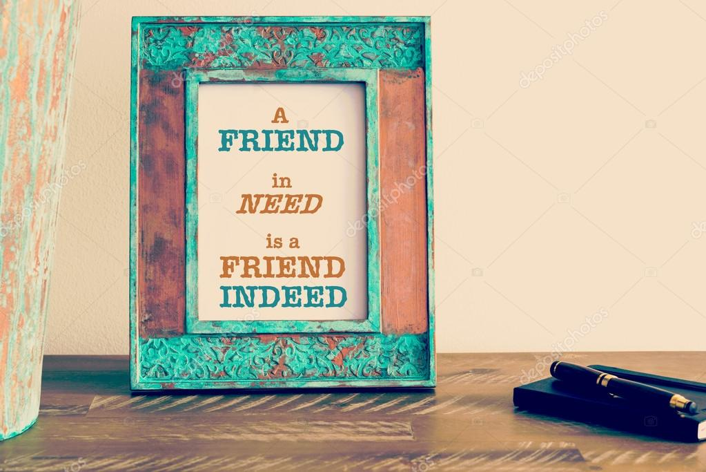 Motivational quote written on vintage photo frame A FRIEND IN NEED ...