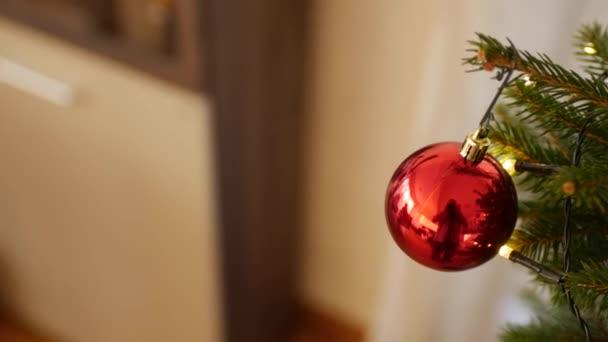 Közelkép egy piros fényes karácsonyi labda az ágak egy igazi karácsonyfa.