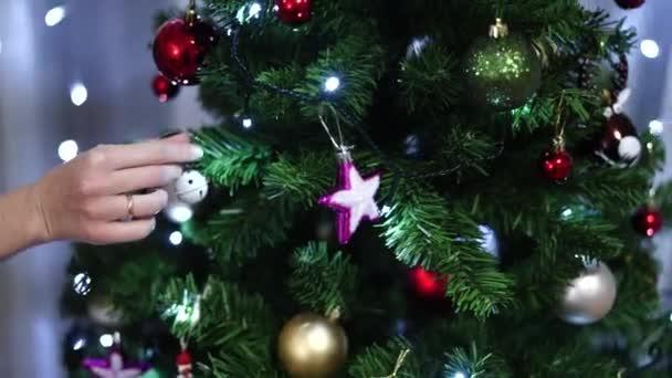 Žena zdobí vánoční stromek. Detailní záběr ženských rukou visící koule.