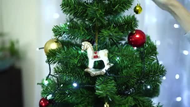 Vánoční hračka houpací kůň na vánočním stromečku, který zdobí mladá žena.