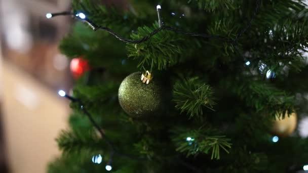 Detailní záběr zdobeného vánočního stromečku s věnec světla.