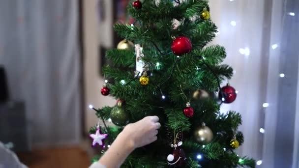 Egy karácsonyfát díszítő nő, közelkép kezekről, amint karácsonyi labdákat tapogatnak..