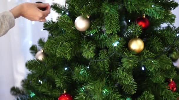 Detailní záběr ženských rukou, zdobí vánoční stromek.