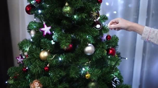 Žena zdobí vánoční stromek s míčky.