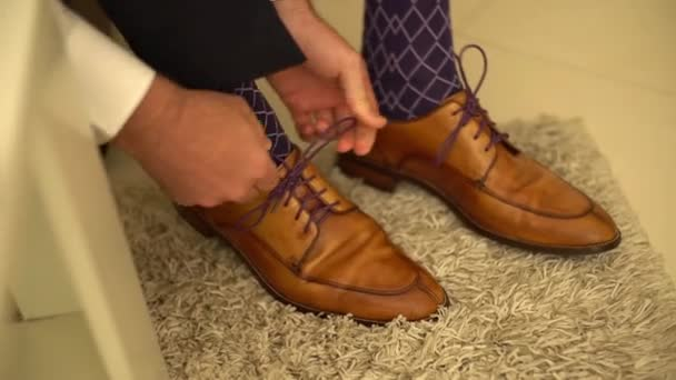 the man puts on his shoes and ties his shoelaces
