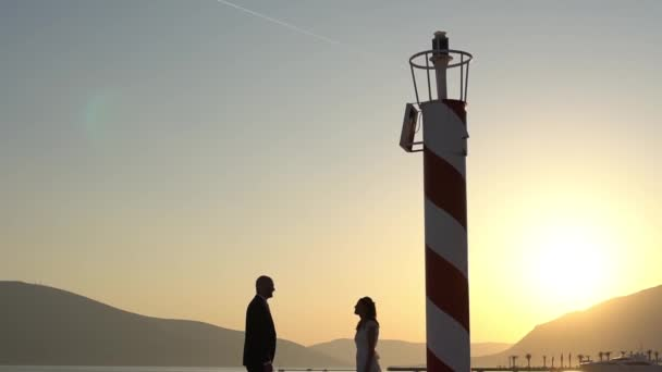the bride and groom are embracing on the pier in Porto Montenegro near the lighthouse, an airplane is flying over them