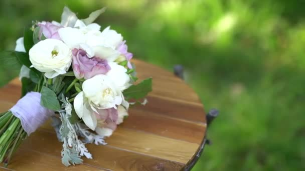 the brides bouquet lies on a wooden stand outdoors