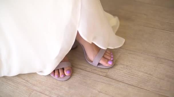 nohy nevěsty v půvabných sandálech vykukují zpod sukně