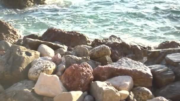 velké mokré kameny na pobřeží, vlny je omývají