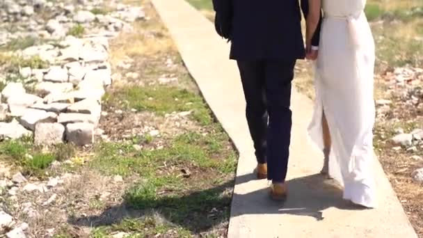 bride and groom walking down the road to the beach holding hands