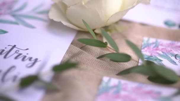 Wedding invitation cards with watercolor drawings, flowers and twigs lie on pastel fabric - close-up