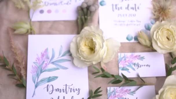 Svatební pozvánky s akvarelovými kresbami, květinami a větvičkami leží na pastelové tkanině