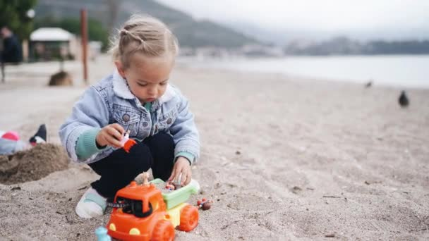 Little girl plays in the sand on the beach. Two-year-old child in a denim jacket playing with plastic toys on a sandy beach in spring.