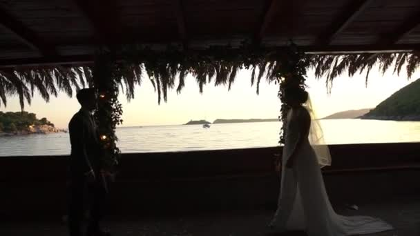 silhouettes of the bride and groom, approaching each other near the wedding arch in the evening against the backdrop of the sea