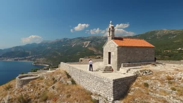 Couple dancing on the observation deck near the ancient church of Sveti Savva in Montenegro