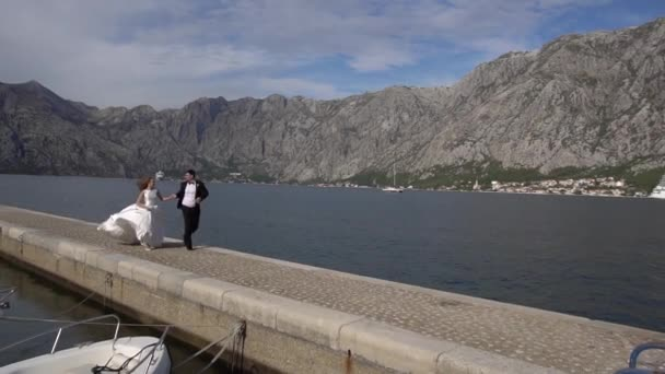 Kotor, Montenegro - 29 july 2020: The bride and groom are running along the pier, holding hands. Behind them is a large cruise ship.
