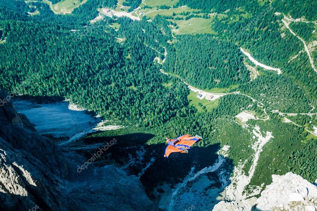 BASE jumper jumping off a big cliff in Dolomites,Italy, breathta