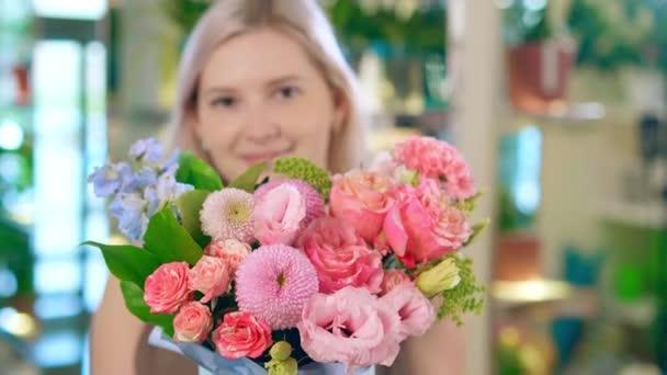 Virágos mosolyog, és azt mutatja, rózsaszín virágok csokor a kamera