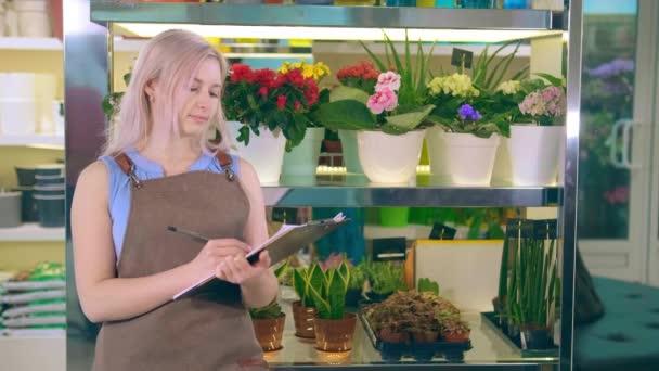 Květinářství drží poznámky a píše stojící proti květináče