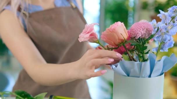 Florist hands prepare tender bouquet in light blue hat box