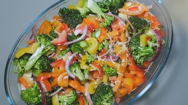 Cheese falls on fresh raw fruit and vegetables salad on dish