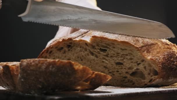 Osoba v rukavicích krájí plátek teplého chleba na dřevěné desce