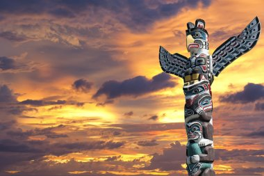 A totem wood pole in the gold cloudy background