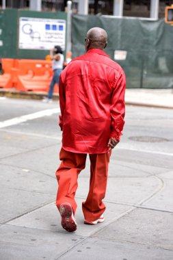 NEW YORK, USA - JUNE 15, 2015 - Red dressed black man walking in Harlem on weekday